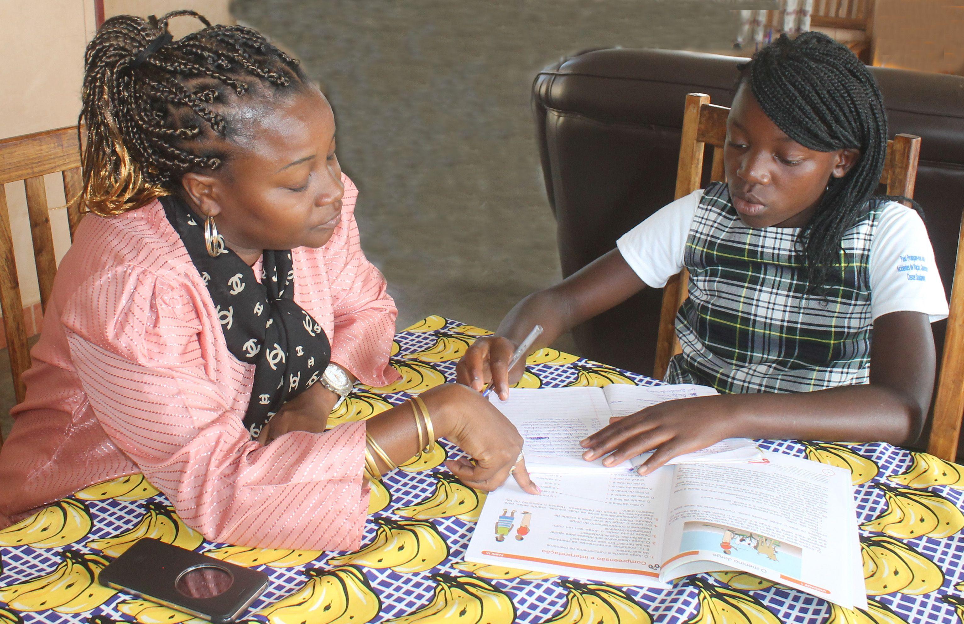 Iyana och hennes barnbymamma Clarence sitter vid bordet och gör läxorna.