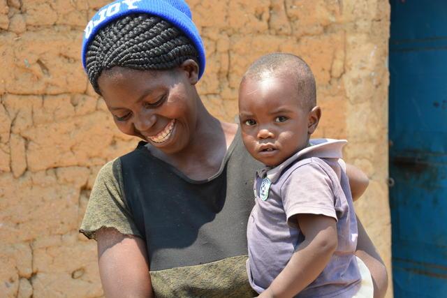 Kvinna med barn i sin famn.
