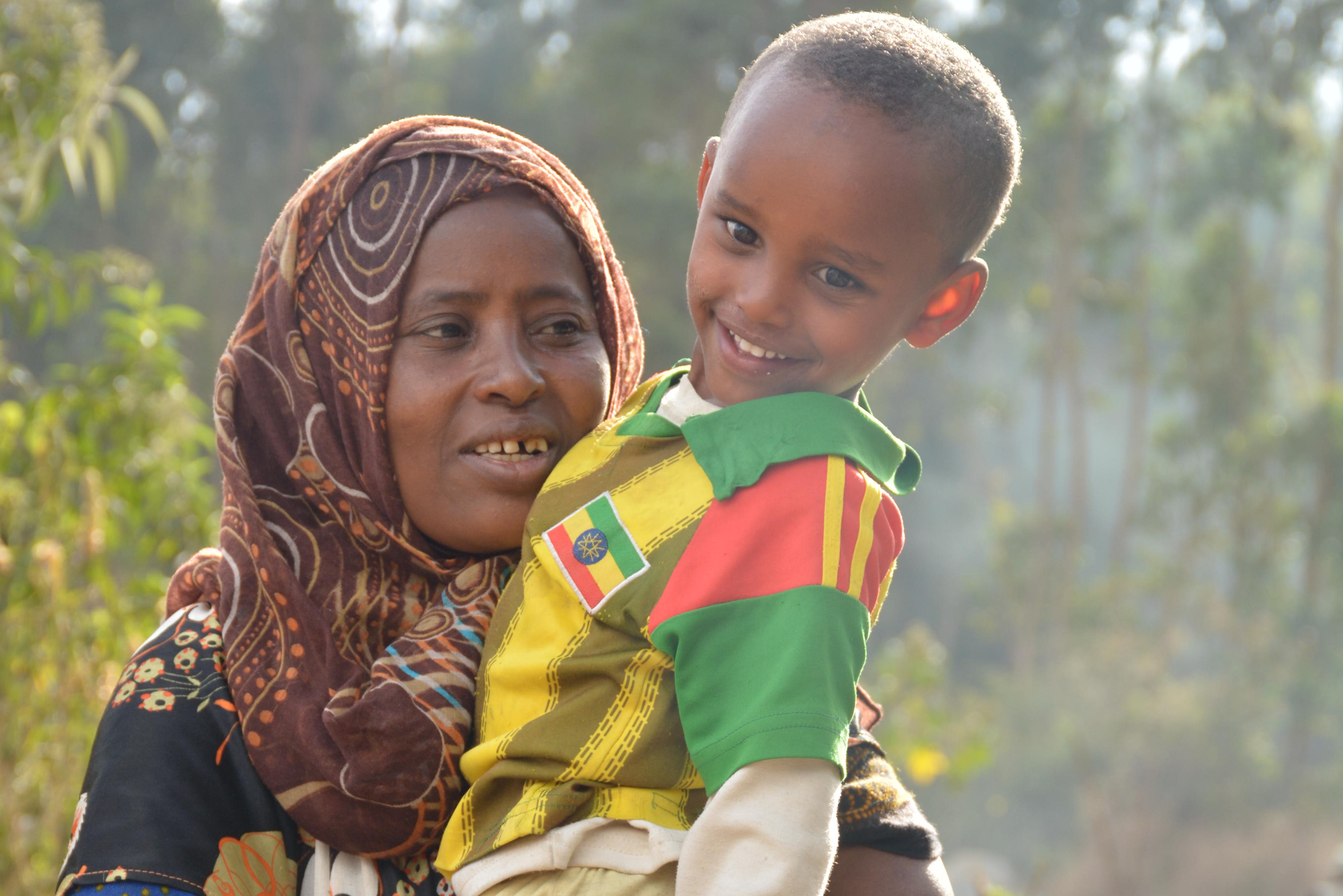 En kvinna bär på sin son. Bilden är tagen utomhus med träd i bakgrunden.