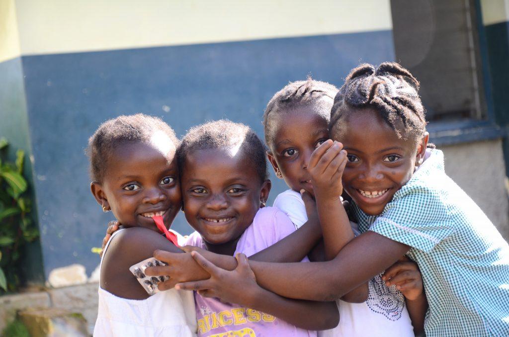 Fyra flickor kramar varandra och ler.
