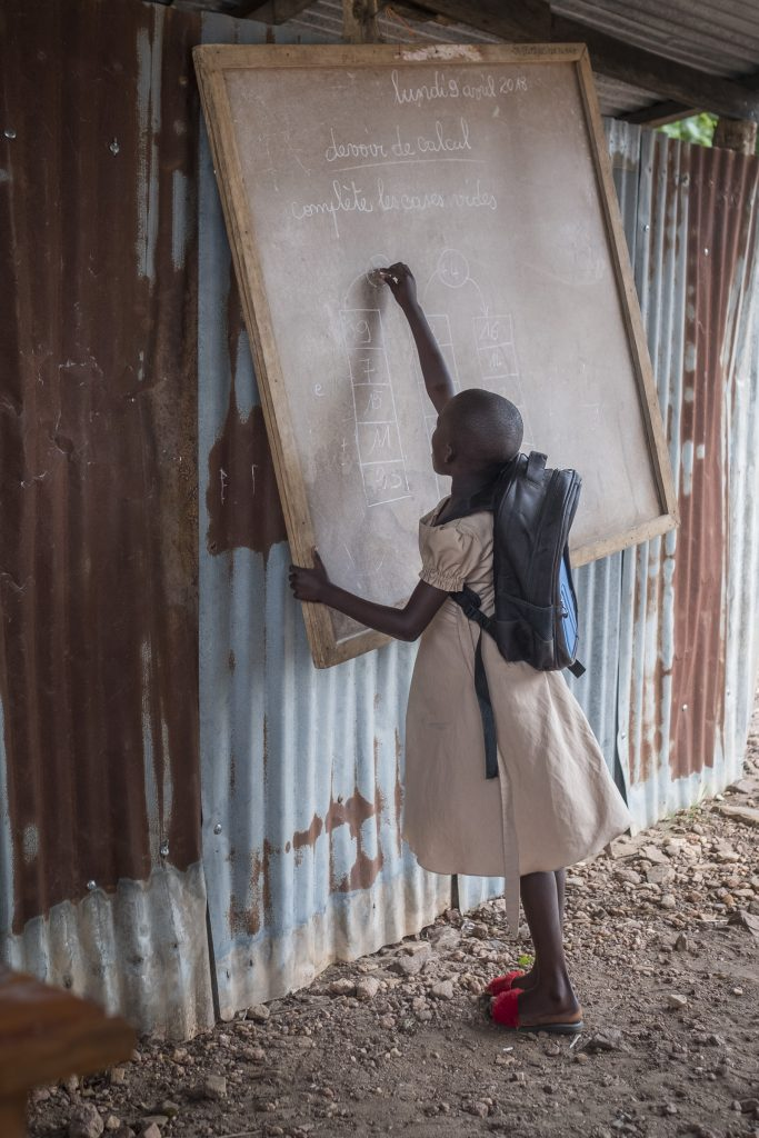 Flicka skriver på en svart tavla mot en vägg utomhus.