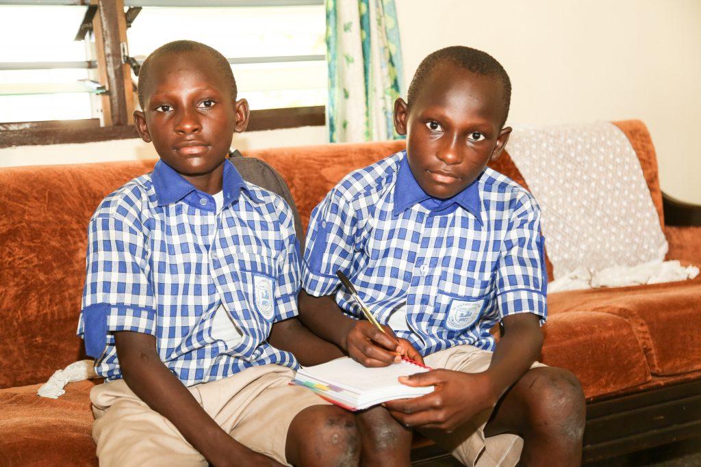 Tvillingarna Fadu och Sidu sitter bredvid varandra och skriver i en bok.