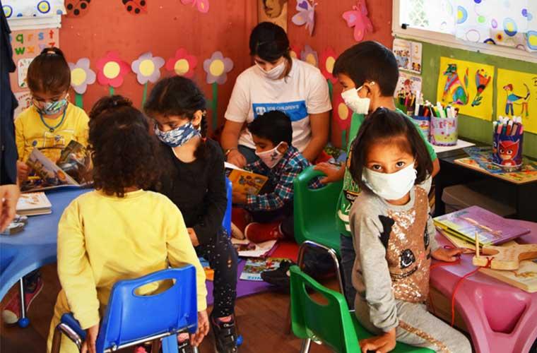 läsande barn i skola med munskydd mot färggranna väggar