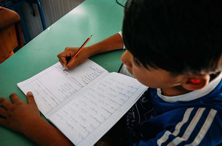 pojke skriver i bok mot grön bänk