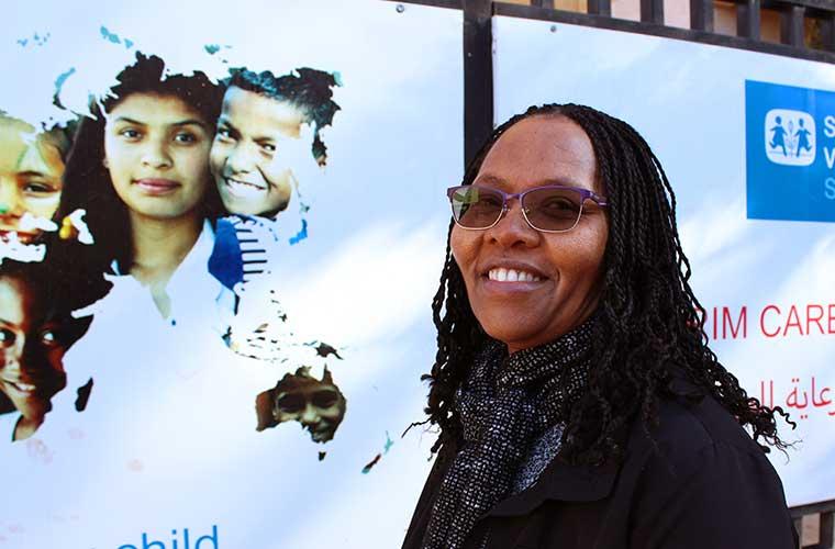 kvinna i flätor och solglasögon med svarta kläder mot vit vägg ler