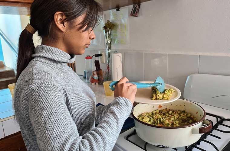 flicka med mörkt hår i tofs i grå tröja lägger upp zucchiniröra på sin tallrik