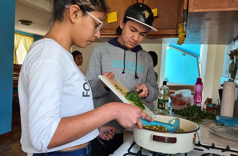 En flicka och pojke hjälps åt att hälla i chili stekapannan