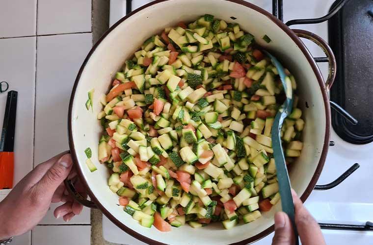 vit kastrull på spis med hackade bitar av zucchini och tomater