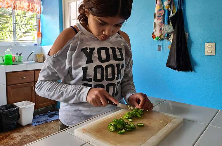 flicka i tröja med text hackar grön chili med kniv