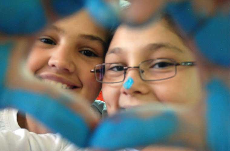 barn med glada ögon som tittar igenom ett hjärta format med en hand blå av målarfärg