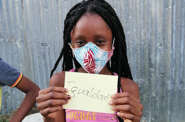 Flicka med munskydd håller en lapp där det står Igualdad