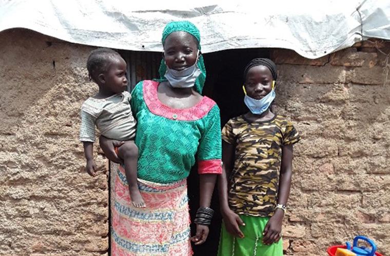 rassem och hennes mamma och lillasyster står med munskydd framför en tegelvägg