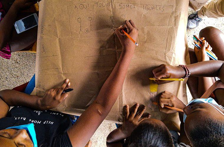 grupparbete där flera sitter runt ett stort papper och ritar streckgubbar
