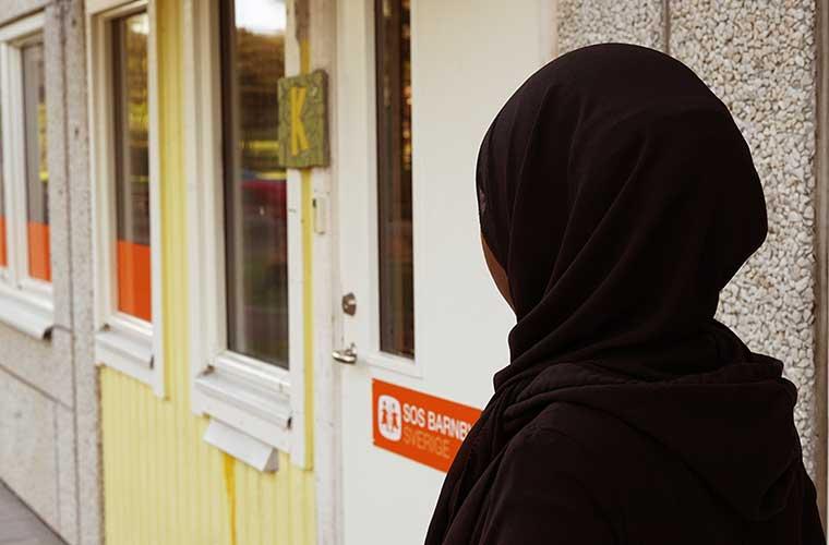kvinna med svart sjal står framför sos barnbyars lokaler