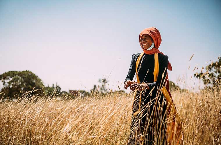 ung kvinna med orange huvudbonad står på ett fält och ler
