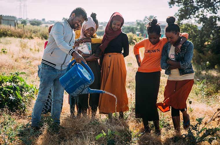 ungdomar står på ett fält och vattnar med vattenkanna