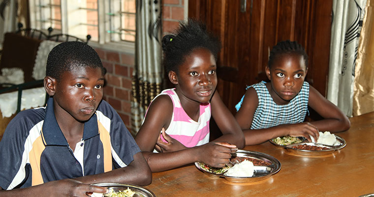 tre barn vid ett bord äter mat