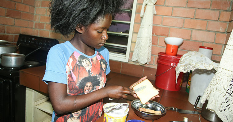 flicka brer en smörgås i ett kök med röda tegelväggar