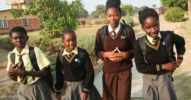 fyra flickor i skoluniform går på en väg