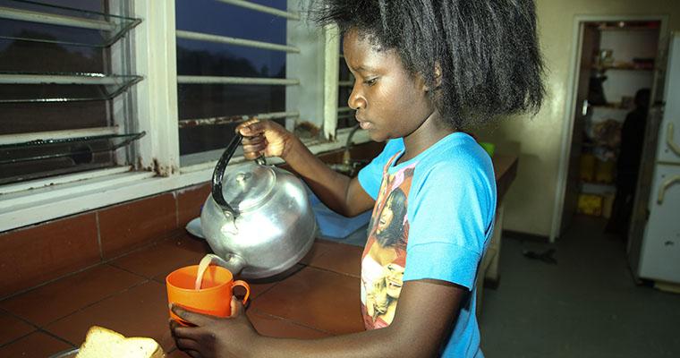 flicka i blå tröja häller upp te