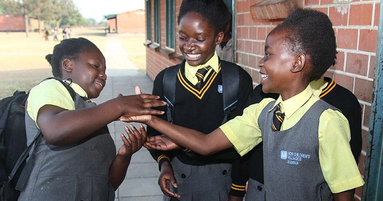 Flickor skojar och hälsar på varandra i skoluniform