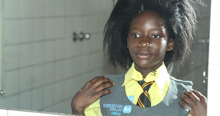 flicka i skoluniform tittar i spegel