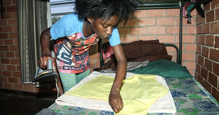flicka stryker en gul skjorta med säng som strykbräda.