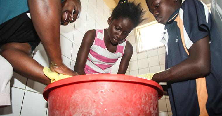 flicka tvättar kläder i en röd plastbalja