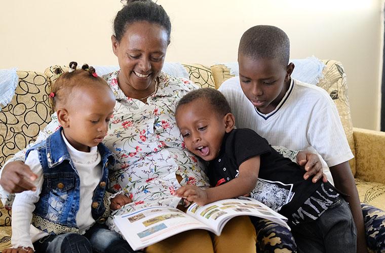 sos-mamma i blommig skjorta och ler sitter i soffa med tre nyfikna barn och en bok i knät ena barnet pekar i boken